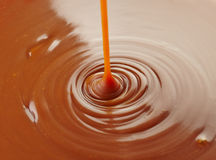 Sweet caramel sauce. Pouring sweet caramel sauce on caramel background royalty free stock photography