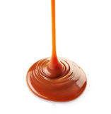 Sweet caramel sauce. Pouring sweet caramel sauce on a white background royalty free stock photography