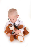 Sweet Caring Child Doctor. Caring Child Doctor Checking a Teddy Bear's Heartbeat on White Stock Images