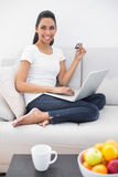 Sweet casual woman home shopping with her notebook. Smiling at camera Stock Photo