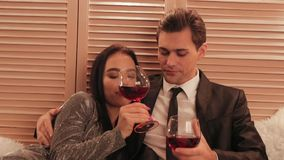 Sweet caucasian couple cheers for the new year and drink wine in a hotel celebrating their anniversary slow motion. Sweet caucasian couple cheers for the new stock footage