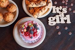 Sweet cheese cake with fresh berries and yoghurt cream and wooden sign Its A Girl. Baby shower party sweets. Stock Image