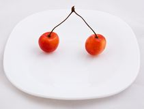 Sweet cherries. Two cherries on white plate Royalty Free Stock Image