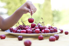 Sweet cherries. Plate with cherries and a children's hand with cherries Stock Photo