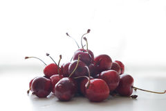 Sweet cherries. Heap of wet sweet cherries on white table Stock Images