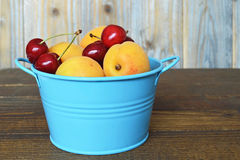 Sweet cherries and apricots in a blue metal bowl Stock Photos