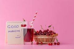 Sweet cherries in a basket and glass of juice on pink  backgroun Stock Photo