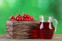 Sweet cherries. In basket with juice in glass jug on wooden table Stock Image