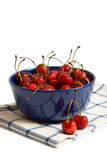 Sweet cherries in the blue cup. S on white background royalty free stock photos