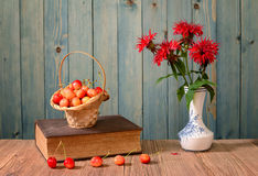 Sweet cherries, books and flowers in a vase Stock Photo