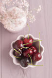 Sweet cherries in bowl and baby's breath flower on pale pink wooden table Stock Photography