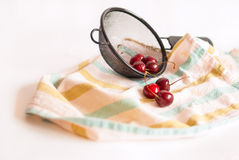 Sweet cherries in a colander on a striped towel. Fresh washed sweet cherries in a black colander on a striped towel; white background Stock Images
