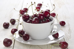 Sweet cherries in a cup. And on wooden table Royalty Free Stock Photos