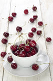 Sweet cherries in a cup. And on wooden table Stock Image