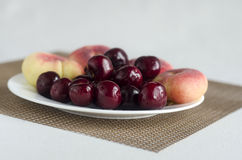 Sweet cherries and donut peaches. On the plate Stock Photography
