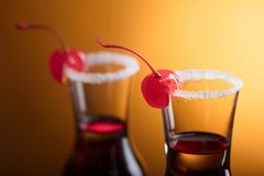 Sweet cherries on glasses of liquor. Sweet cherries on glasses of liquor garnished with sugar . Copy space for your text Royalty Free Stock Photos