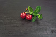 Sweet cherries in golden vase on black table and mint. Sweet Red cherries in golden vase on black table and mint royalty free stock photography