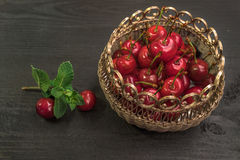 Sweet cherries in golden vase on black table and mint. Sweet Red cherries in golden vase on black table and mint stock photography