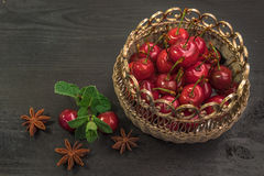 Sweet cherries in golden vase on black table and mint. Sweet Red cherries in golden vase on black table and mint stock illustration