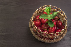 Sweet cherries in golden vase on black table and mint. Sweet Red cherries in golden vase on black table and mint royalty free illustration