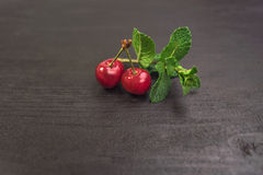 Sweet cherries in golden vase on black table and mint. Sweet Red cherries on black table and mint stock illustration