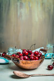 Sweet cherries in old copper pot with glass jars and spoon on light  blue rustic wooden background Royalty Free Stock Photos