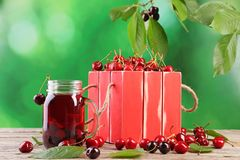 Sweet cherries. In red crate with juice in glass jar on wooden table Stock Photos