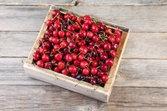 Sweet cherries. In crate on grey wooden table Royalty Free Stock Image