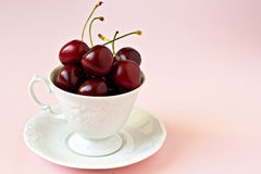 Sweet cherries in a white cup Stock Images