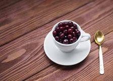 Sweet cherries in a white cup and a teaspoon on a wooden table, selected focus stock photo
