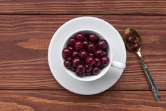 Sweet cherries in a white cup and a teaspoon on a wooden table, selected focus, top view royalty free stock photography
