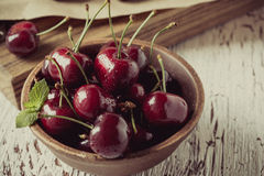 Sweet cherries  on wooden background,  retro style, grained. Sweet cherries  in ceramic bowl on wooden background,  retro style, grained, selective focus Royalty Free Stock Photography