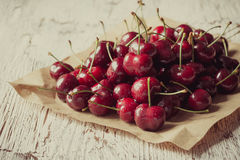 Sweet cherries  on wooden background,  retro style, grained. Sweet cherries  on craft paper on wooden background,  retro style, grained, selective focus Royalty Free Stock Images