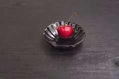 Sweet cherry in black shell on black table. Sweet Red cherry in black shell plate on black table royalty free stock photo