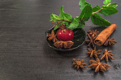 Sweet cherry on black table with cinnamon , star anise and mint. Sweet Red cherry on black plate , table with cinnamon , star anise and mint stock photography