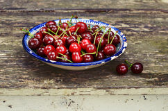 Sweet cherry in blue oriental bowl on wooden background Royalty Free Stock Image