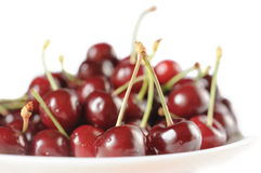 Sweet cherry in a bowl isolated on white. Sweet cherry on a white glass plate, isolated on a white background Royalty Free Stock Photo