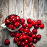 Sweet cherry in the cup on wooden table Royalty Free Stock Photography