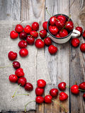 Sweet cherry in the cup on wooden table Stock Photos