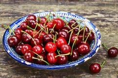 Sweet cherry in oriental ceramic bowl on rusty backdrop Stock Photo