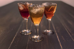 Sweet cherry,plum,quince liquein ice glass on black table. At golden hour stock photo