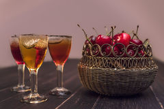 Sweet cherry,plum,quince liquein ice glass on black table and sweet cherries in golden vase Royalty Free Stock Photo