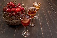 Sweet cherry,plum,quince liquein ice glass on black table and sweet cherries in golden vase. Sweet cherry,plum,quince liquer ice glass and sweet cherries in royalty free stock images