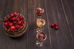 Sweet cherry,plum,quince liquein ice glass on black table and sweet cherries in golden vase Royalty Free Stock Photos