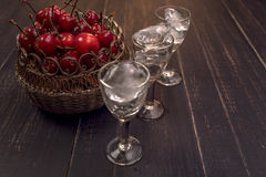 Sweet cherry,plum,quince liquein ice glass on black table and sweet cherries in golden vase Stock Image