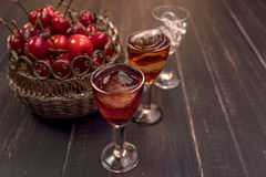 Sweet cherry,plum,quince liquein ice glass on black table and sweet cherries in golden vase Stock Photos