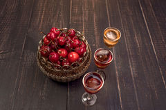 Sweet cherry,plum,quince liquein ice glass on black table and sweet cherries in golden vase. Sweet cherry,plum,quince liquer ice glass and sweet cherries in stock image