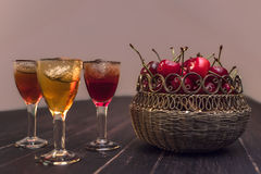Sweet cherry,plum,quince liquer ice glass on black table and sweet cherries in golden vase. Sweet cherry,plum,quince liquer ice glass and sweet cherries in stock images