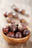 Sweet chestnuts. In the wooden bowl on the rustic table Stock Photos