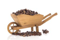 Sweet chestnuts in wheel barrow. Wheel barrow full with sweet chestnuts  over white background Royalty Free Stock Photos